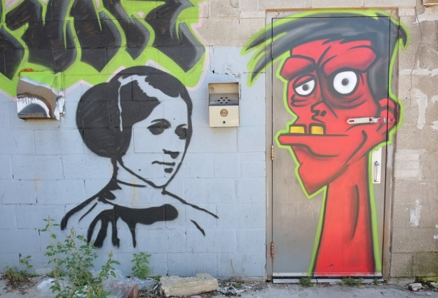 street art in an alley - red man's head, with protruding lower jaw and two large yellow teeth, white eyes, on a door, black and white picture of Star Wars Princess Leia on the wall beside