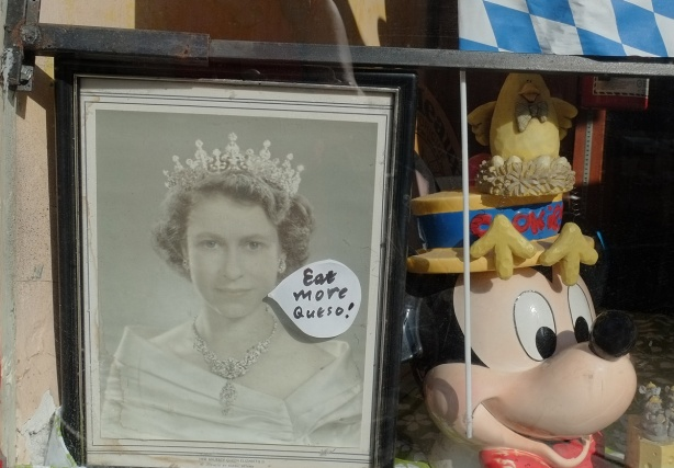 old framed black and white photo of Queen Elizabeth, on top it someone has given her a word bubble that says eat more queso (Spanish for cheese), in the window of a cheese store