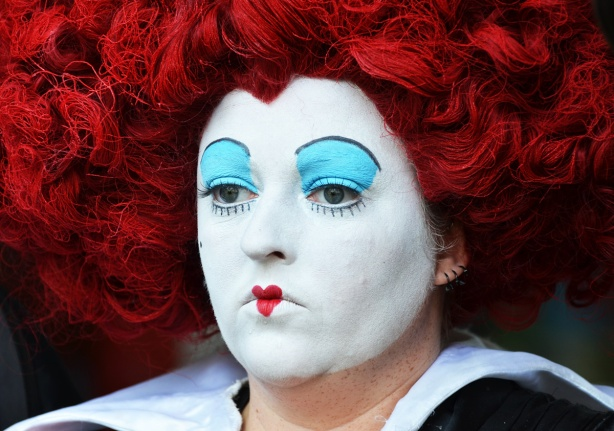 woman dress as the Queen of Hearts, head only, curly red hair, white face paint, tiny red heart on lips