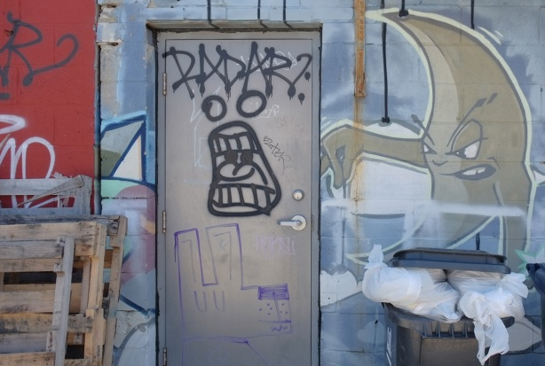 street art in an alley - word radar on grey metal door, with screaming face below, on the wall beside is a moon shpaed figure, with arm out and seems to be holding something in its fingers but nothing there, garbage bins (real) below