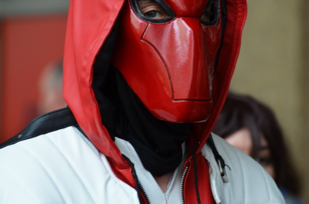 man in red leather mask, holes for eyes but nothing else,