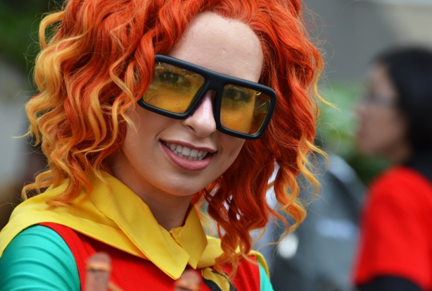 a woman dressed as Robin, Boy Wonder, reddish orange wig, and large glasses