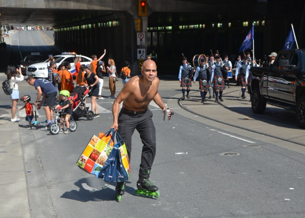 a man roller blades past the parade, water bottle in one hand, grocery bags in the other, he is topless, labour Day parade on Queen St West,