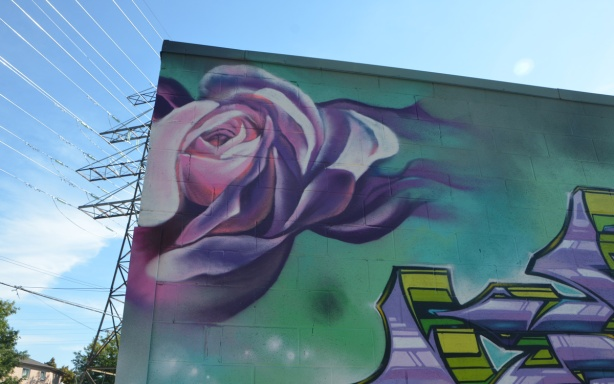 a painting of a rose, very realistic, at the top corner of the side of a building, hydro poles and wires in the background