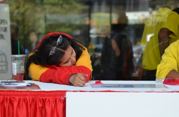 a woman lies on her arms on a table, sitting at the table, as she works outside at Fan Expo