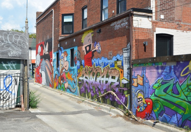 in a popart mural by Matt Gondek and Jackson, in an alley, along the wall of one side, mickey mouse, sylvester the cat, spaceman spliff, and calvin and hobbes
