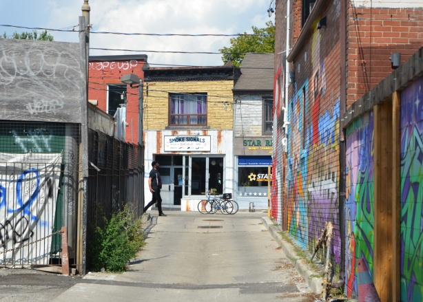 looking north up Skey Lane to Smoke Signals, a barbecue restaurant on Dundas West, a man is walking by on the sidewalk