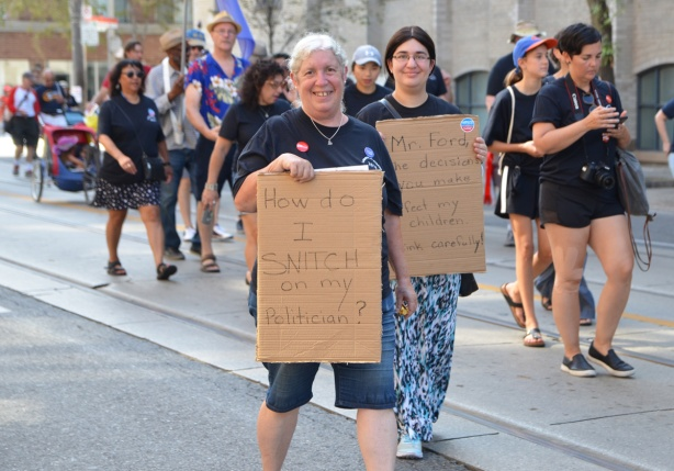 labour Day parade on Queen St West, two women carry brown cardboard signs, one says How do I snitch on my politician? and the other talks about policies affecting education ofchildren