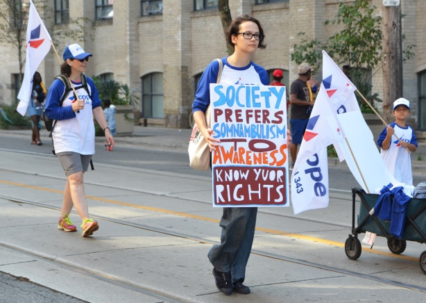 a young person walks in the labour Day parade on Queen St West, carrying a sign that says society prefers somnambulism to awareness, know your rights