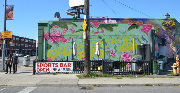 the side of a building covered with a mural of flowers and the words St. Clair Gardens