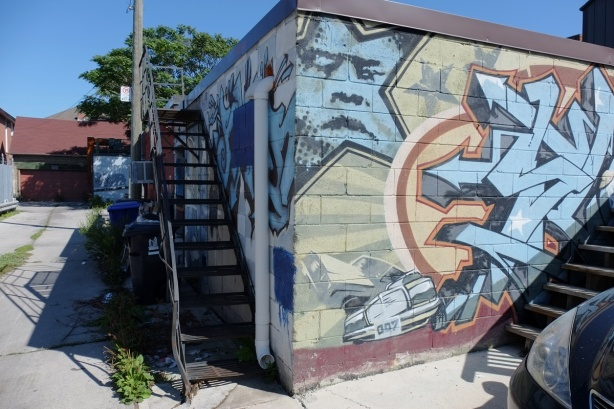 street art in an alley - corner of a concrete block building, metal staircase as well, blue star with a man's face inside it, a racing car near the bottom with licence plate 007