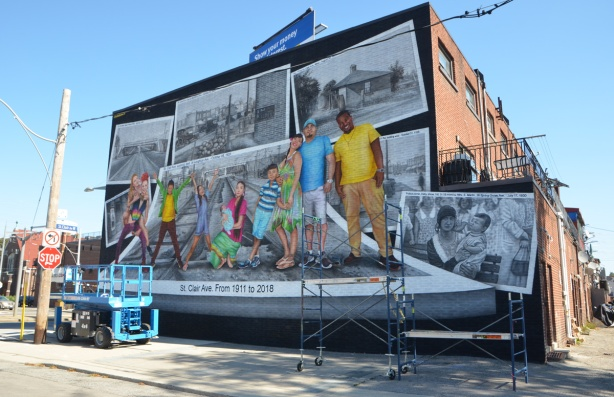 new mural on the side of a 2 storey building, a series of vintage black and white photos of the area and people, with paintings of 8 modern people in colour