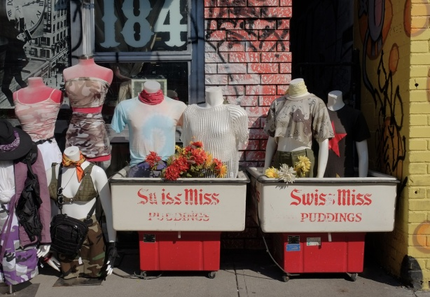 3 half mannequins dressed in tops, standing in two old containers that say swiss miss puddings