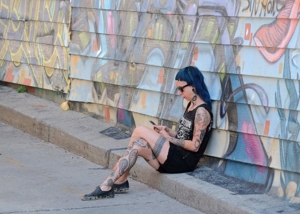 a young woman with blue hair and many tattoos is looking at her phone as she sits on a kerb