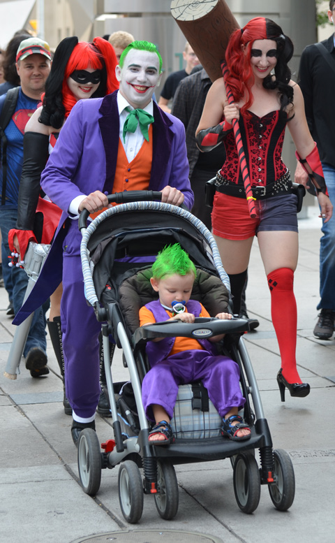 man dressed up as Joker pushes a stroller with a young boy also dressed as the Joker with green hair and purple suit