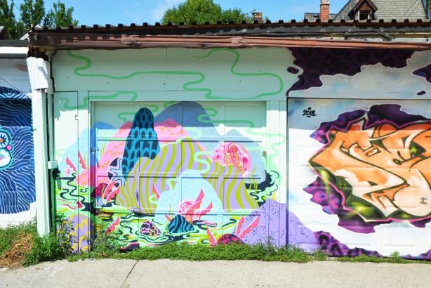 three murals in a lane
