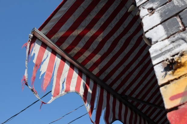 red and white striped awning above a store, tattered
