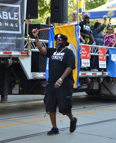 labour Day parade on Queen St West, a black man waves a union flag, wearing a black t shirt with the words No Justice No Peace. Some other people are riding on a flat bed truck behind him, with posters that say Pay Equality for all
