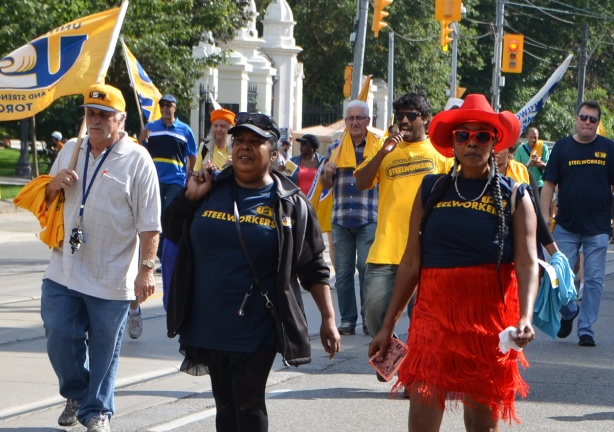 members of United Steelworkers walk in Labour Day parade including a woman in red cowboy hat and red frilly skirt