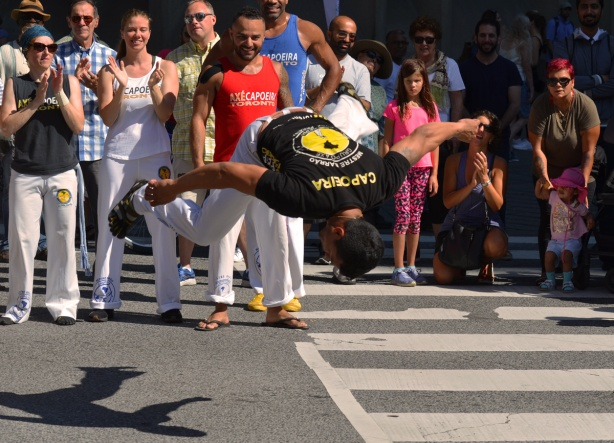 a man is flipping upside down in front of an audience on the sidewalk