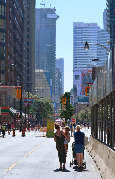 two women walk with their young children, strollers, down Yonge Street during OPen Streets, downtown Toronto in the background