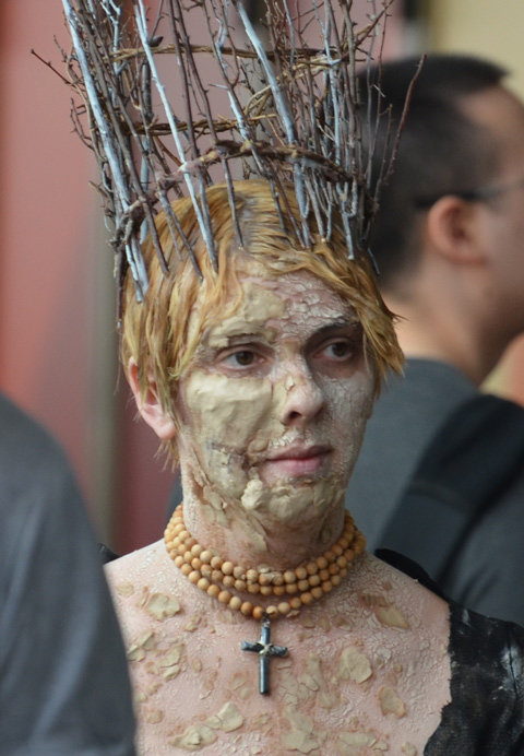 a woman wearing a tall crown made of sticks, three strands of yellow beads and a cross around her neck, lots of make up to make her face look mottled and bumpy