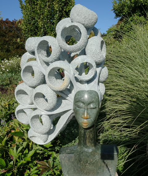 sculpture of a woman's head, eyes closed, with lots of rings of lighter stone hair, title is Windy Day