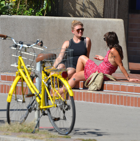 two women sitting on the steps of a building having a discussion, a yellow bike is in the foreground