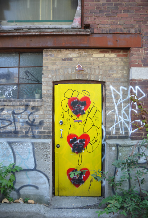 a door painted yellow with three large red hearts on it