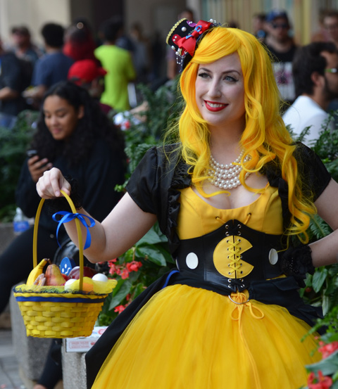 woman in yellow wig, and matching yellow dress, carrying a yellow basket