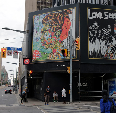 mural above the sidewalk, as people walk by, Yonge Street street sign, traffic,