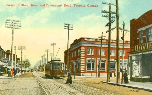 vintage coloured postcard of the intersection of Bloor and Dovercourt in Toronto, hydro poles, brick buildings, streetcar, woman crossing road, no cars