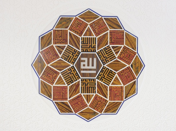 medallion of stone, calligraphy, arabic, on a white wall