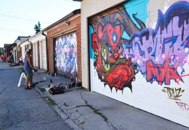 garage doors being painted with street art murals, laneway