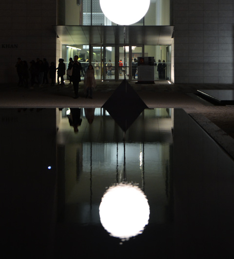 in front of the Aga Khan museum, a large white lit ball is reflected in the pool of water