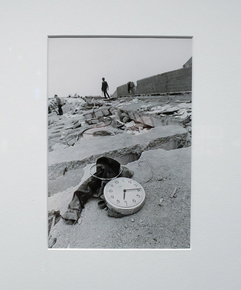 an old black and white photograph of Mexico city after the 1985 earthquake, a pair of pants and a clock on top of a flattened building, some people in the distance
