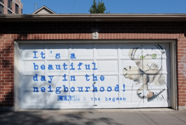 white garage door with blue words that say It's a beautiful day in the neighbourhood, also a picture of a hand puppet,