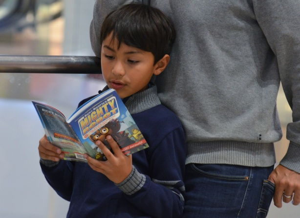 a young boy leans against his father as he reads a book, MIghty Robot, at the Eaton Centre
