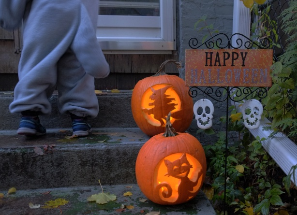 two carved pumpkins on front door steps, one carved with a witch and the other with a cat, also a sign that says Happy Halloween