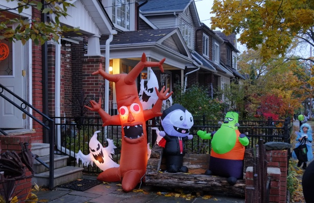 Halloween night, early evening, not quite dark, a street scene where one house has a lot of inflatable characters on the lawn as decorations