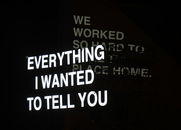 two large signs at Scarborough Nuit Blanche, from the installation called Everything I wanted to tell you. Back lights say We worked so hard to make this place home