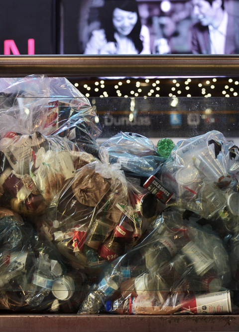 clear plastic bags full of trash are pilled up against a clear wall at Yonge Dundas square