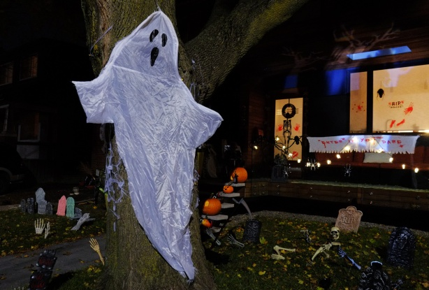 ghost made of fabric tacked to a tree in front of a house with porch and front yard all decorated for Halloween