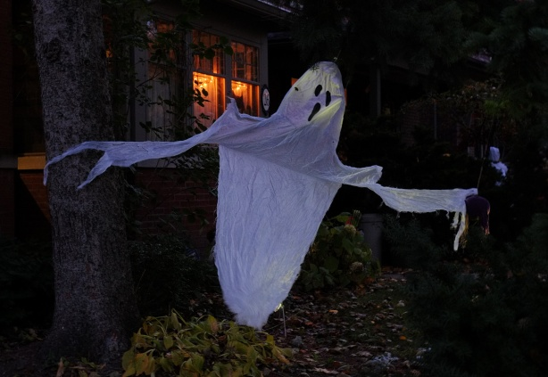 ghost made of white fabric waving in the breeze in front of a house, night time, window lights on