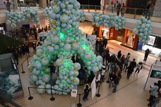 piles of inflatable globes are arranged at Scarborough Town Centre, people are walking around them and through a tunnel made of them