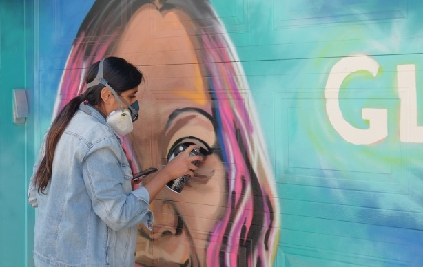 spray painting the eye on a mural