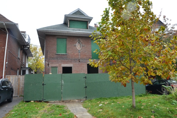 large square brick house from the early 1900s, windows boarded up and green plywood hoardings in front