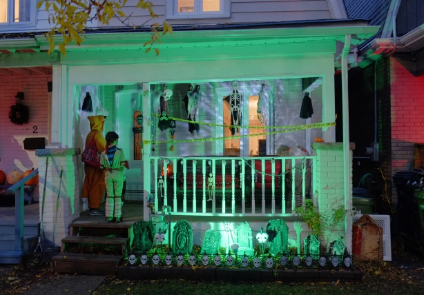 Halloween night, trick or treaters at the door of a house with lots of tombstones and skulls, also the porch is lit by an eerie green light.