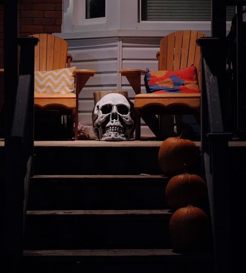 a skull sits on the porch at the top of the stairs.