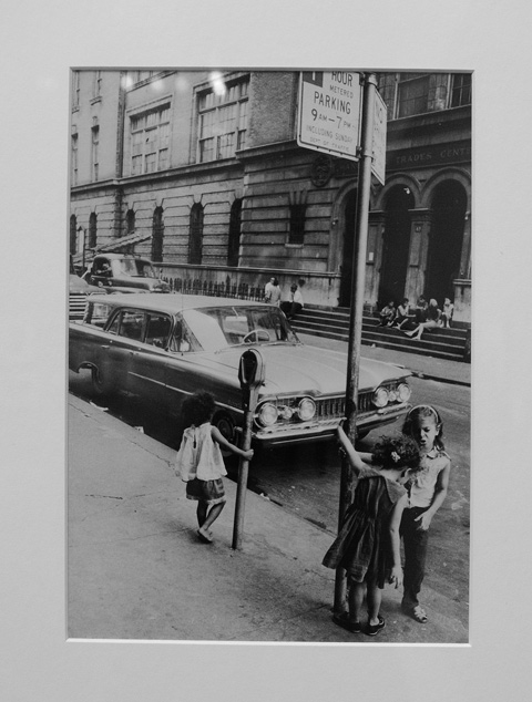 old photo from the 1960s, 3 children play on the sidewalk by a car that is parked on the street